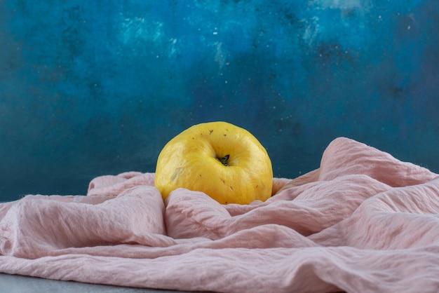 Fruit de coing jaune isolé sur nappe rose.