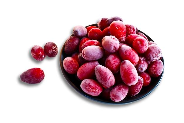 Fruit de cornouiller rouge congelé sur fond blanc