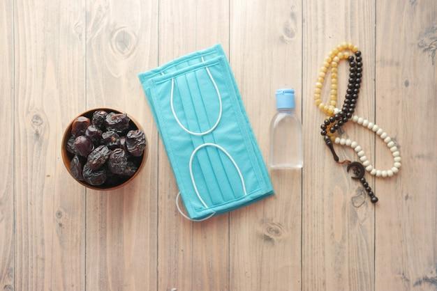 Fruit de datte frais dans un bol chapelet de prière désinfectant pour les mains et masque sur le sol