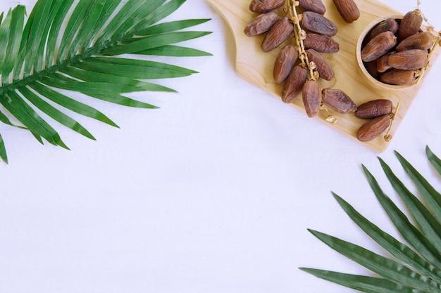Fruit de dattes séchées avec espace de copie pour votre produit, feuilles de palmier vertes, minimum