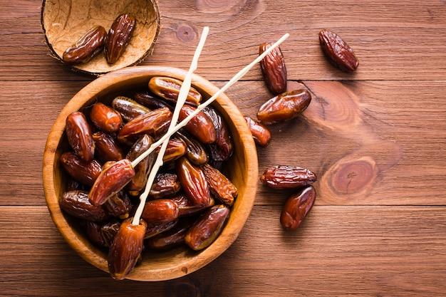 Fruit de dattes sucrées séchées dans un bol en bois sur la table. vue de dessus