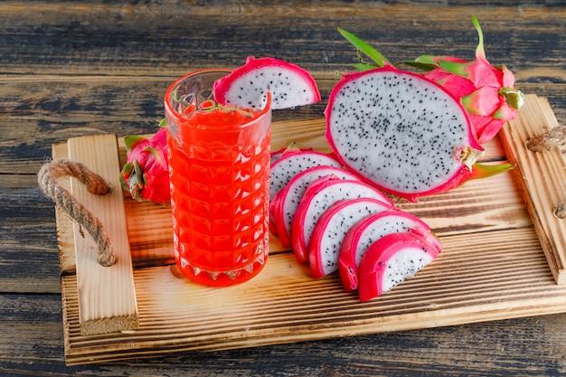 Fruit du dragon dans un bac avec du jus de vue grand angle sur une table en bois