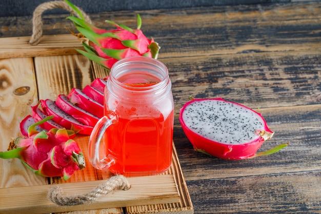 Fruit du dragon avec du jus dans un plateau sur table en bois, vue grand angle.
