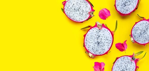 Fruit du dragon ou pitaya avec des fleurs de bougainvilliers sur fond jaune.