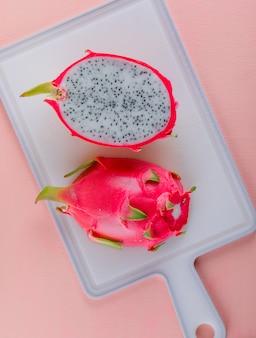 Fruit du dragon sur rose et planche à découper. vue de dessus.