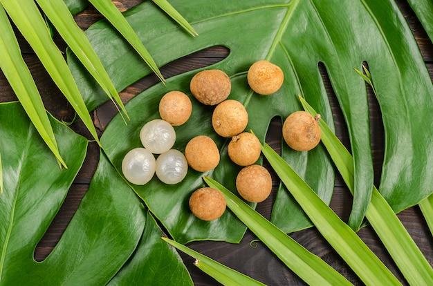 Fruit exotique longan, lam-yay ou dragon's eye. plusieurs fruits sur monstera et feuilles de palmier.