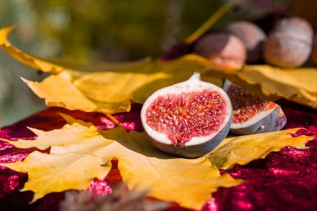 Fruit de figue juteux et parfumé sur feuille d'érable jaune.