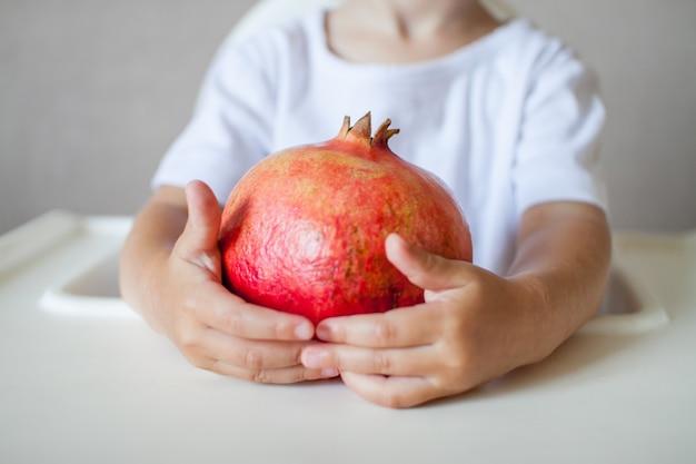 Fruit de grenade dans les mains d'un petit enfant en gros plan le symbole du rosh du nouvel an juif