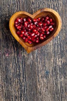 Fruit de grenade rouge et mûr avec des grains dans une assiette en forme de cœur grenade délicieuse et saine ...