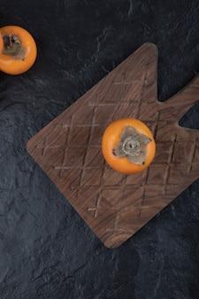 Fruit de kaki fuyu entier sur une planche à découper en bois
