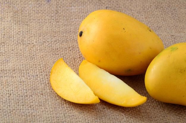 Fruit de la mangue avec une tranche sur un tissu de sac