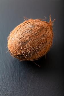 Fruit de noix de coco tropical unique organique sur fond de pierre ardoise noire avec espace de copie