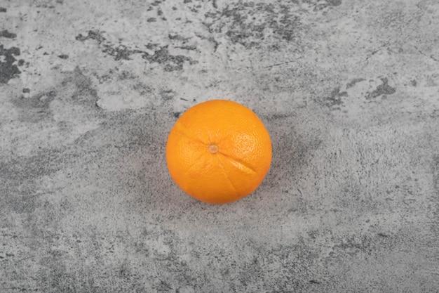 Un fruit orange sain et frais entier sur une table en pierre.