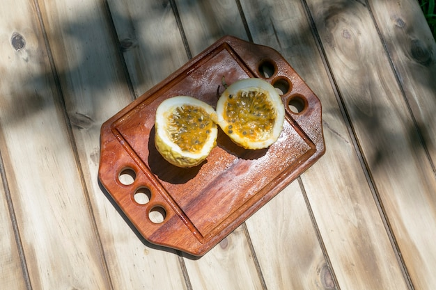 Fruit de la passion coupé en deux sur un plateau en bois