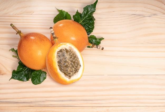 Fruit de la passion avec des feuilles en fond de bois fruit de la passion ou maracuja avec des feuilles