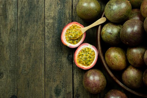 Fruit de la passion frais dans un bol en bois sur la surface de la table