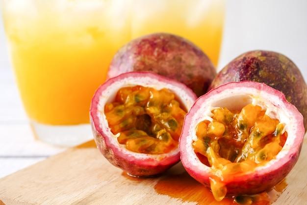 Fruit de la passion frais et jus sur une table en bois.