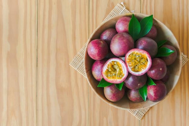 Fruit de la passion mûr dans un bol en bois sur une table en bois en vue de dessus plat poser avec espace de copie.
