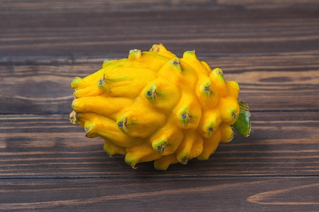 Fruit pitahaya jaune mûr, allongé sur un fond de planches de bois