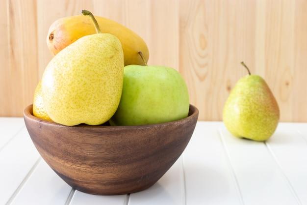 Fruit, pomme, poire, mangue dans un bol en bois. récolte d'automne.