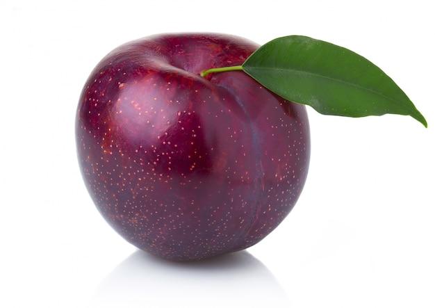Fruit de prune pourpre mûr avec des feuilles vertes isolées
