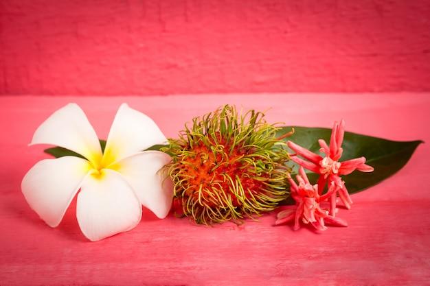 Fruit de ramboutan sur bois couleur rose avec fleur