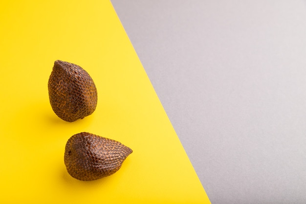 Fruit de salak ou de serpent sur fond pastel gris et jaune. vue latérale, copiez l'espace. tropical,