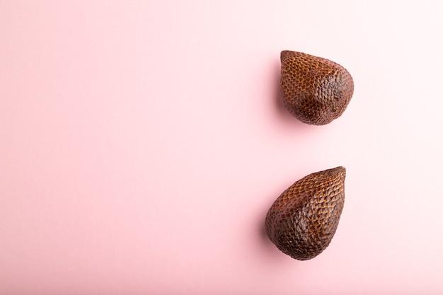 Fruit de salak ou de serpent sur fond pastel rose. vue de dessus, mise à plat, espace de copie. tropical,