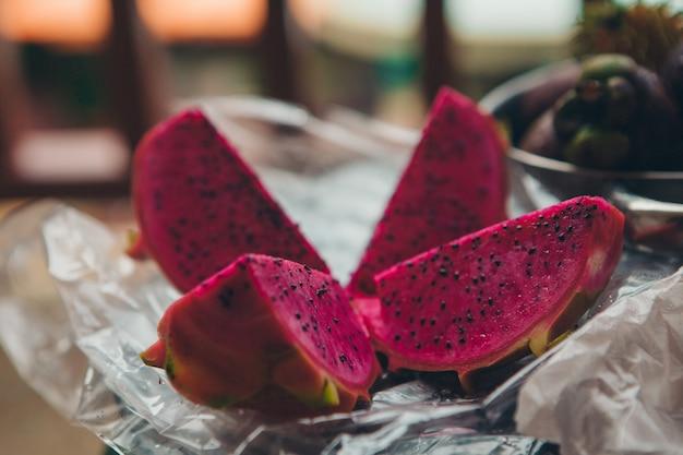 Fruit thaïlandais: oeil de dragon. nourriture rose coupée en morceaux sur un gros plan de plaque