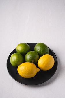 Fruits aigres de citron vert et citron en plaque noire sur blanc