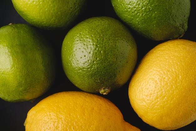 Fruits aigres de citron vert et citron en plaque noire, vue de dessus, vitamines et aliments sains