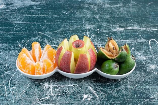 Fruits d'automne isolés dans des soucoupes blanches.