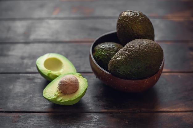 Fruits d'avocat entiers dans un bol fabriqué à partir de coquilles de noix de coco et coupés en deux se trouvent à côté sur un fond en bois sombre.