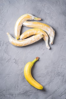 Fruits de banane enveloppés dans du plastique extensible sur une surface grise