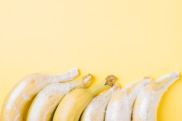 Fruits de banane enveloppés dans du plastique extensible sur une surface jaune
