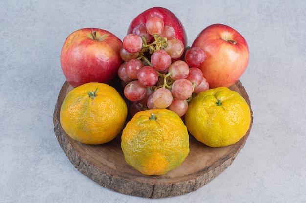 Fruits biologiques frais. pomme, raisins et mandarines sur planche de bois.