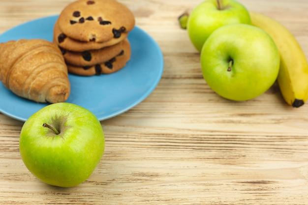 Fruits avec des biscuits et une plaque de croissant sur une table en bois