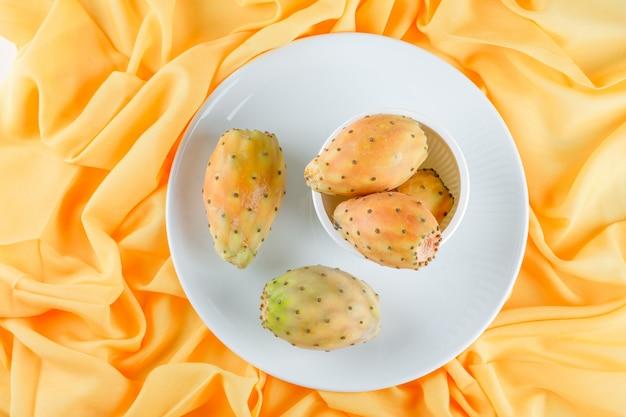 Fruits de cactus dans un bol et une assiette sur une surface textile jaune