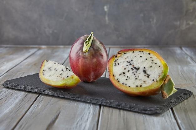 Fruits de cactus de pomme péruvienne entiers et coupés sur un support en bois sur une planche grise. nom scientifique cereus repandus