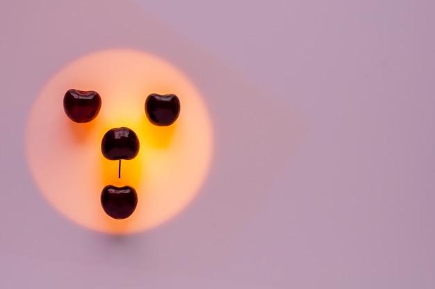 Les fruits de cerise mis sur la lumière de couleur orange définie comme visage de bonheur.