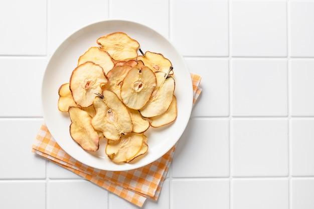 Fruits chips de poire sur fond blanc moderne dessert végétalien sans sucre