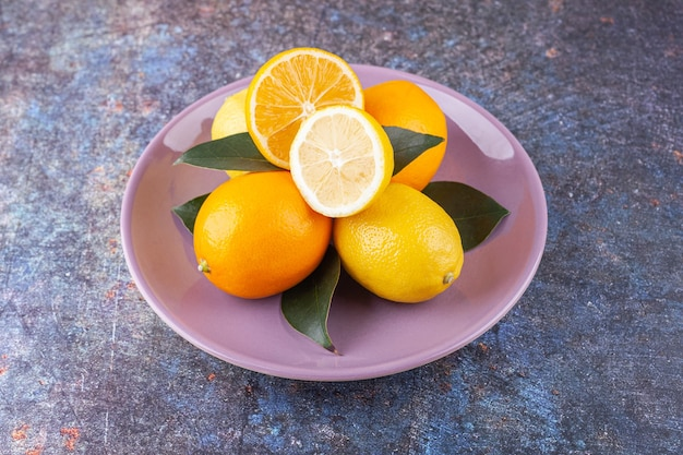Fruits de citron entiers et tranchés placés sur un fond de pierre.