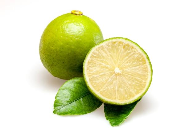 Fruits de citron vert et morceau avec feuilles isolé sur fond blanc