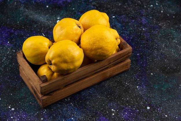 Fruits de coing entiers frais dans une boîte en bois sur une table sombre.