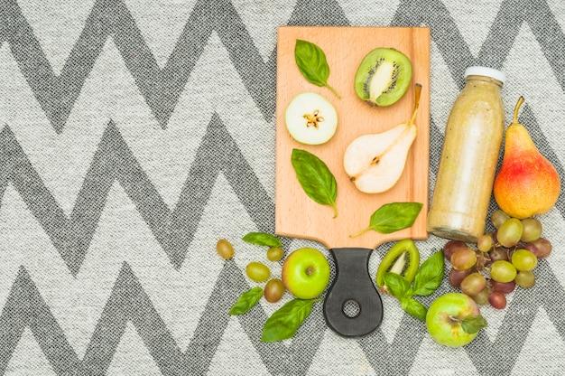 Fruits coupés en deux et bouteille de smoothie sur une nappe à motif textile en zigzag