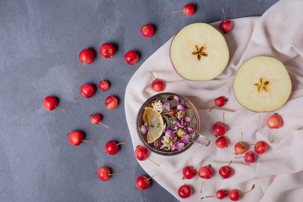 Fruits coupés à moitié, cerises et verre de jus avec tranche de citron et fleurs sur bleu avec nappe