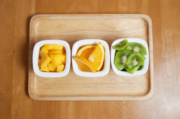 Fruits dans la mini tasse sur le plateau en bois mangue, kiwi et orange