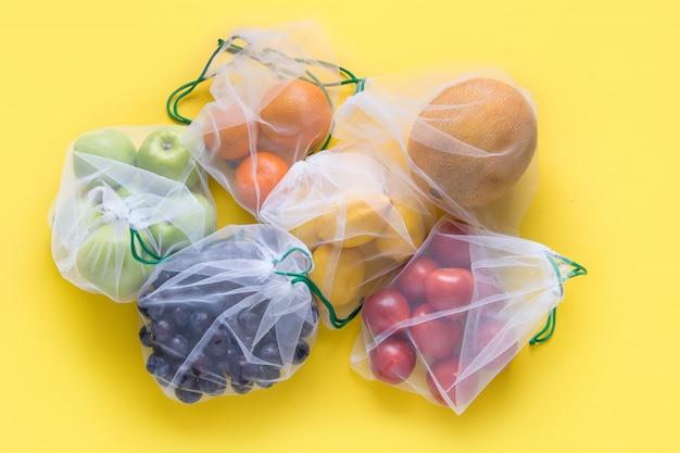 Fruits dans des sacs réutilisables en filet écologique sur fond jaune.