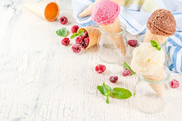Fruits et desserts sucrés d'été, divers arômes de crème glacée dans des cônes roses (framboises), vanille et chocolat à la menthe sur du béton léger