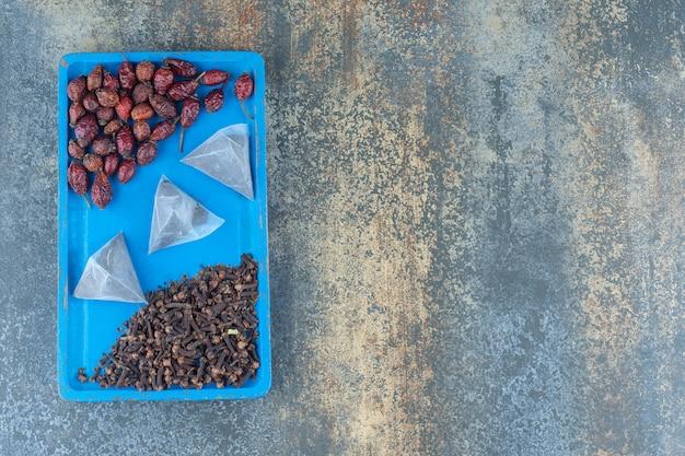 Fruits d'églantier séchés et sachets de thé sur plaque bleue.